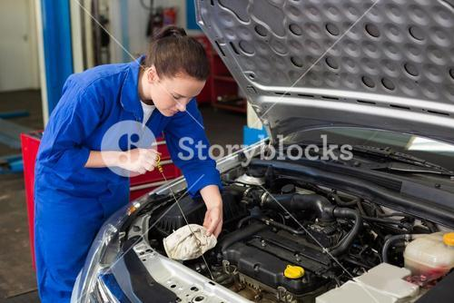 Mechanic checking the oil of car