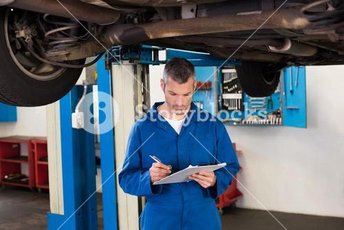 Mechanic writing on a clipboard