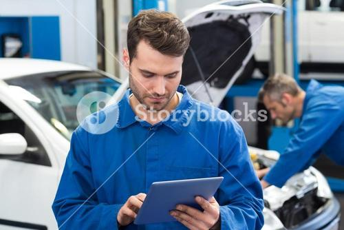 Smiling mechanic using a tablet pc