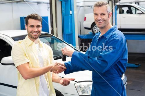 Customer shaking hands with mechanic taking keys
