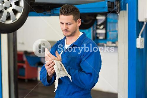 Mechanic wiping hands with rag