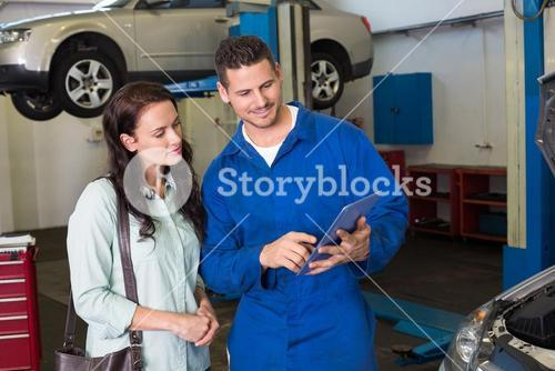 Mechanic showing tablet pc to customer