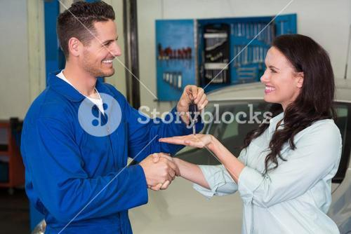 Mechanic giving keys to satisfied customer