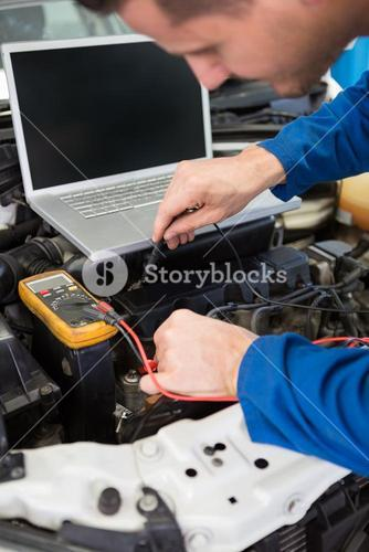 Mechanic using diagnostic tool on engine