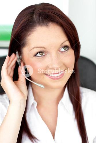 Serious young businesswoman with earpiece in a call center