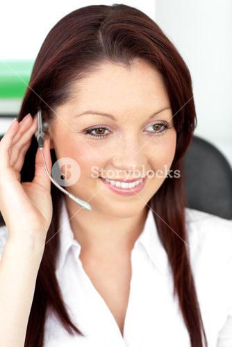 Positive young businesswoman sitting at her desk and wearing earpiece