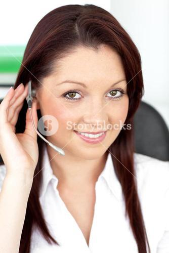Attractive young businesswoman wearing earpiece in a customer service