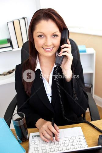 Selfassured businesswoman talking on phone and using her laptop at her desk