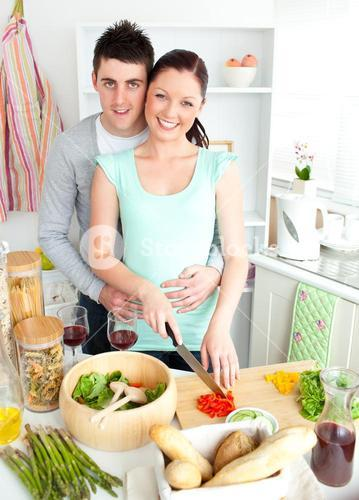 Enamored young couple cutting vegetables in the kitchen