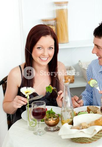 Smiling young couple dining in the kitchen