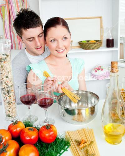 Close couple preparing spaghetti in the kitchen and drinkng wine