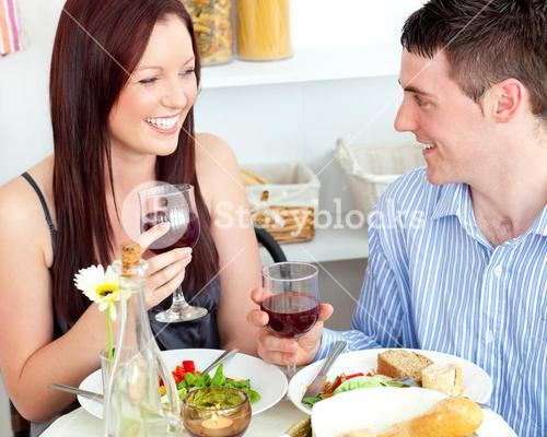 Laughing couple having dinner at home