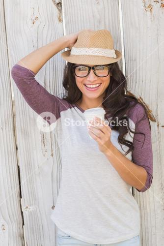Pretty brunette holding take away coffee