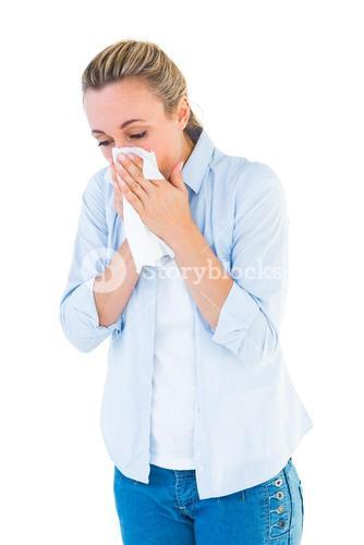 Beautiful blonde blowing nose on tissue