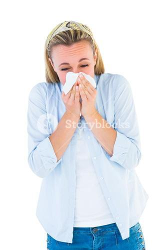 Casual blonde blowing nose on tissue