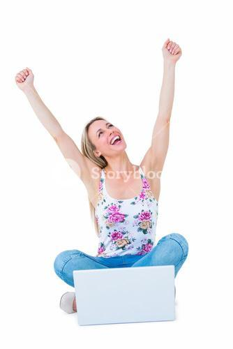 Happy blonde cheering with arms up near her laptop