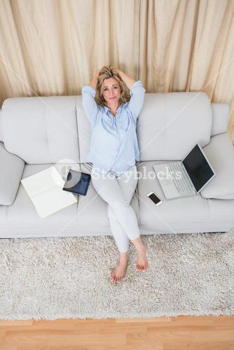 Pretty blonde sitting on couch near wirelesses technology