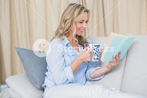 Smiling blonde reading a book with coffee