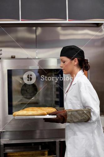 Charming young baker with baguettes