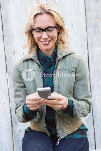 Happy blonde in glasses text messaging