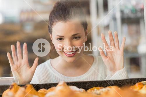 Pretty brunette looking at pastrys