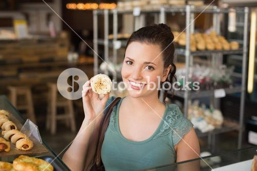 Pretty brunette showing a cupcake