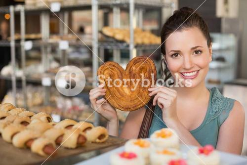 Pretty brunette holding heart shape pastry