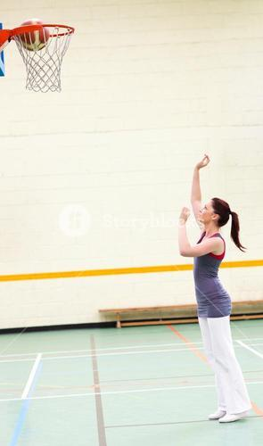 Gifted woman practicing basketball