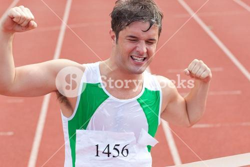 Ecstatic sprinter showing expression of victory in front of the arrival line