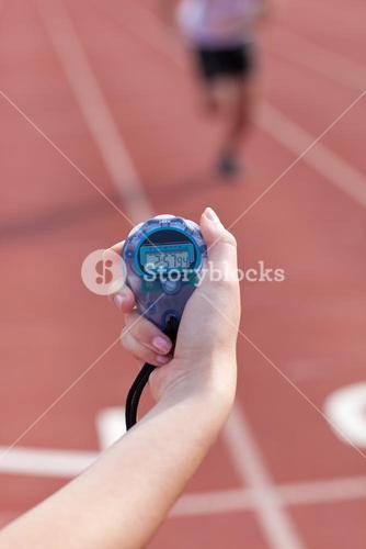 Close up of a woman holding a chronometer to measure performances of a sprinter