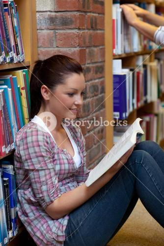 Pretty young woman reading a book sitting on the floor