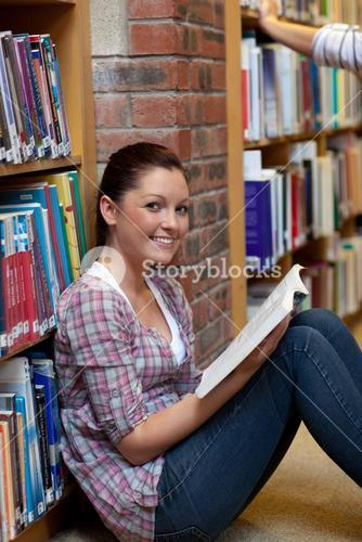 Smiling young woman reading a book sitting on the floor