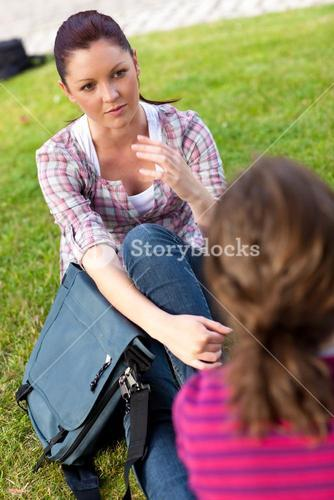Two female friends talking together sitting on the grass