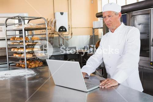 Focused baker using laptop on worktop