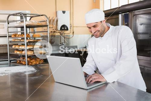 Smiling baker using laptop on worktop