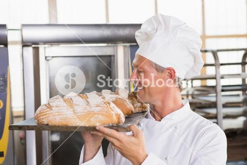 Baker holding tray of bread