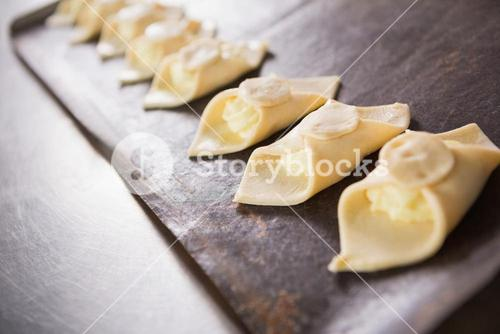 Close up of baker holding tray of raw dough
