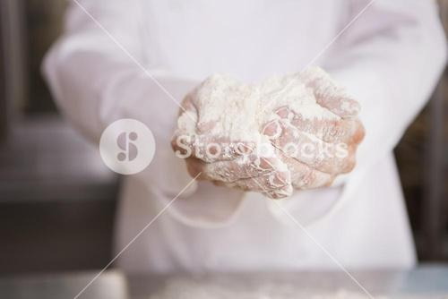 Close up of bakers hands holding flour