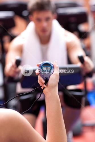 Woman holding a chronometer and man doing physical exercise