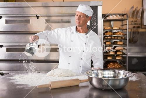 Baker working with scoop and dough