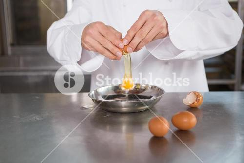 Close up of baker cracking an egg in bowl