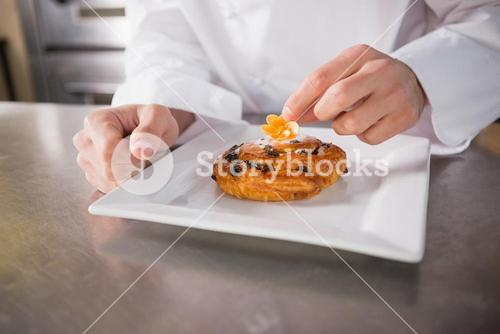 Close up of baker putting flower on the pastry