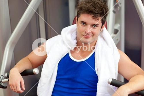 Handsome muscular man using a bench press
