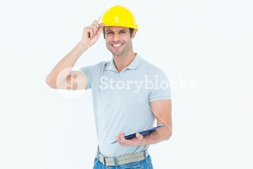Architect wearing hard hat while holding clip board