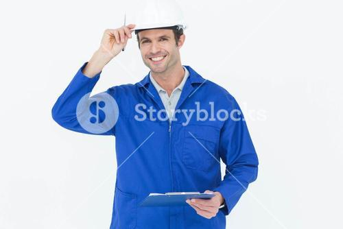 Happy supervisor wearing hard hat while holding clip board