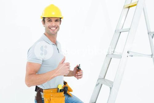 Technician with tools showing thumbs up by step ladder