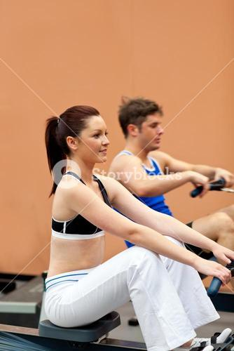 Athletic people using a rower