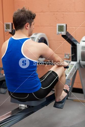 Athletic man using a rower