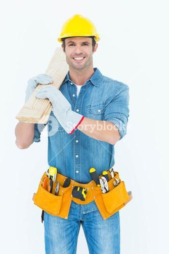 Happy carpenter carrying wooden planks