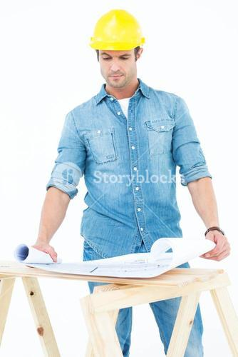 Architect analyzing blueprint at table